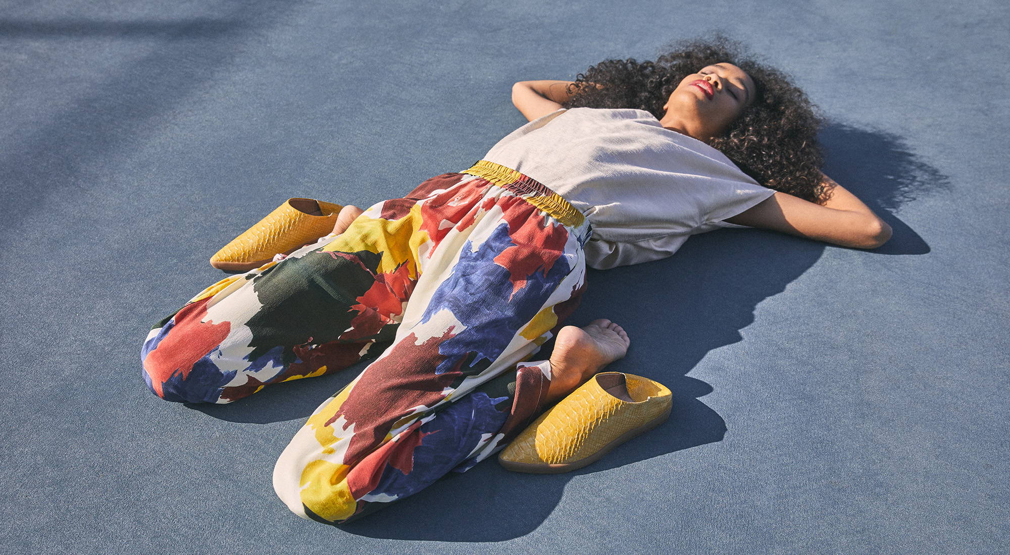 Woman in colorful pants laying on tennis court