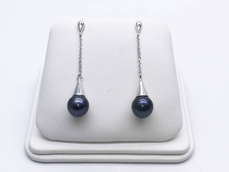 White gold handmade pendant earrings with black beads on a jewellery display stand