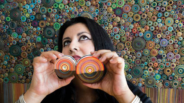 Hadieh Shafie posing with two colored paper art in front of a collage.