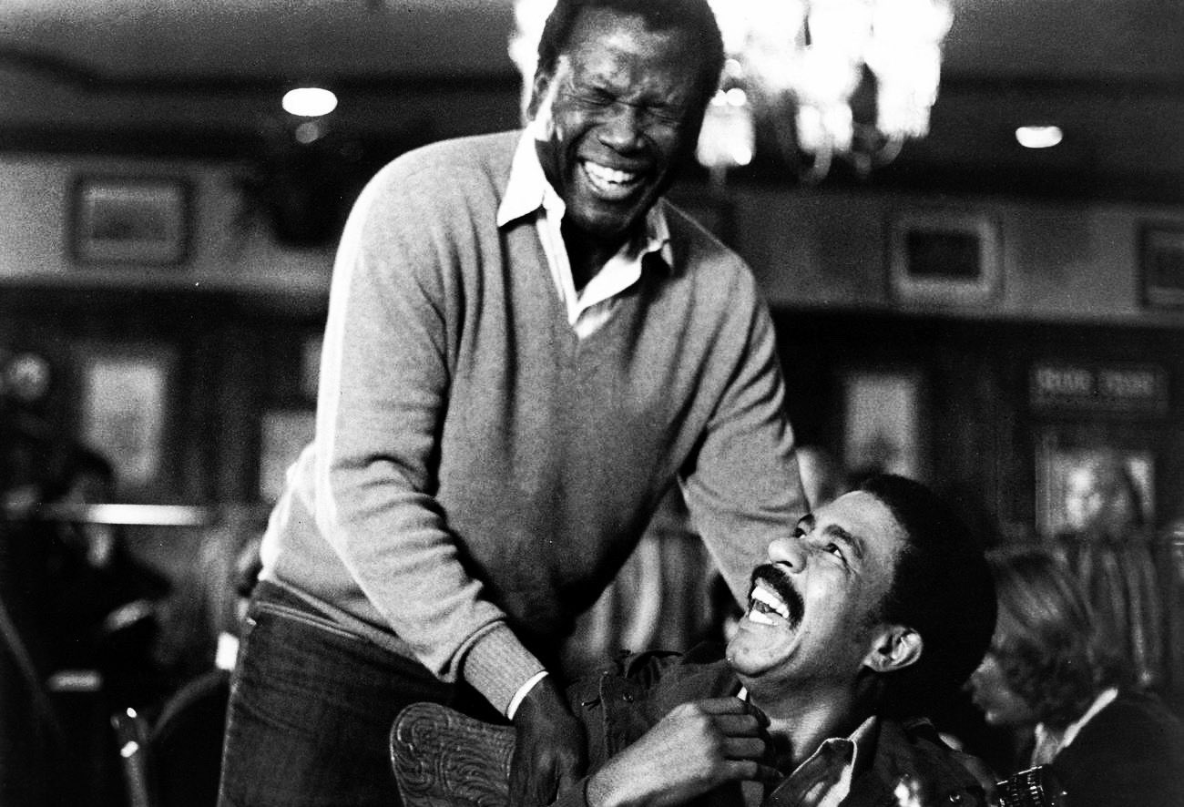 Sidney Poitier and Richard Pryor laughing together on the set of