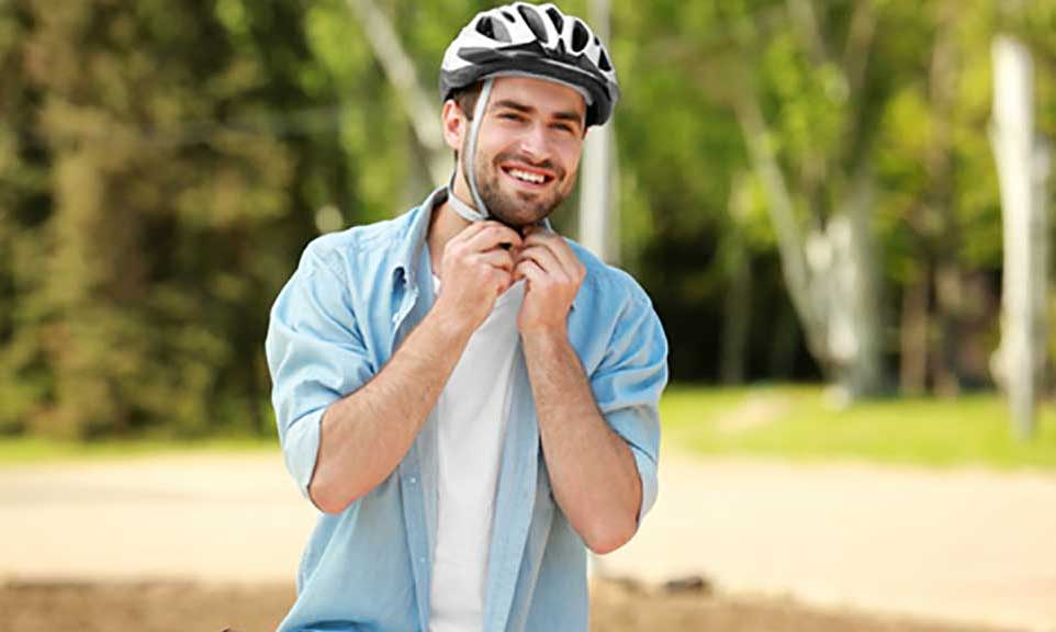 guy putting on a bicycle helmet