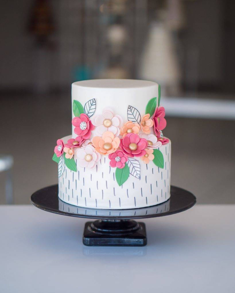 Flower cake made of fondant with white icing and pink and peach flowers. Order your cake today at our bakery for birthdays or special occasions at House of Clarendon in Lancaster, PA