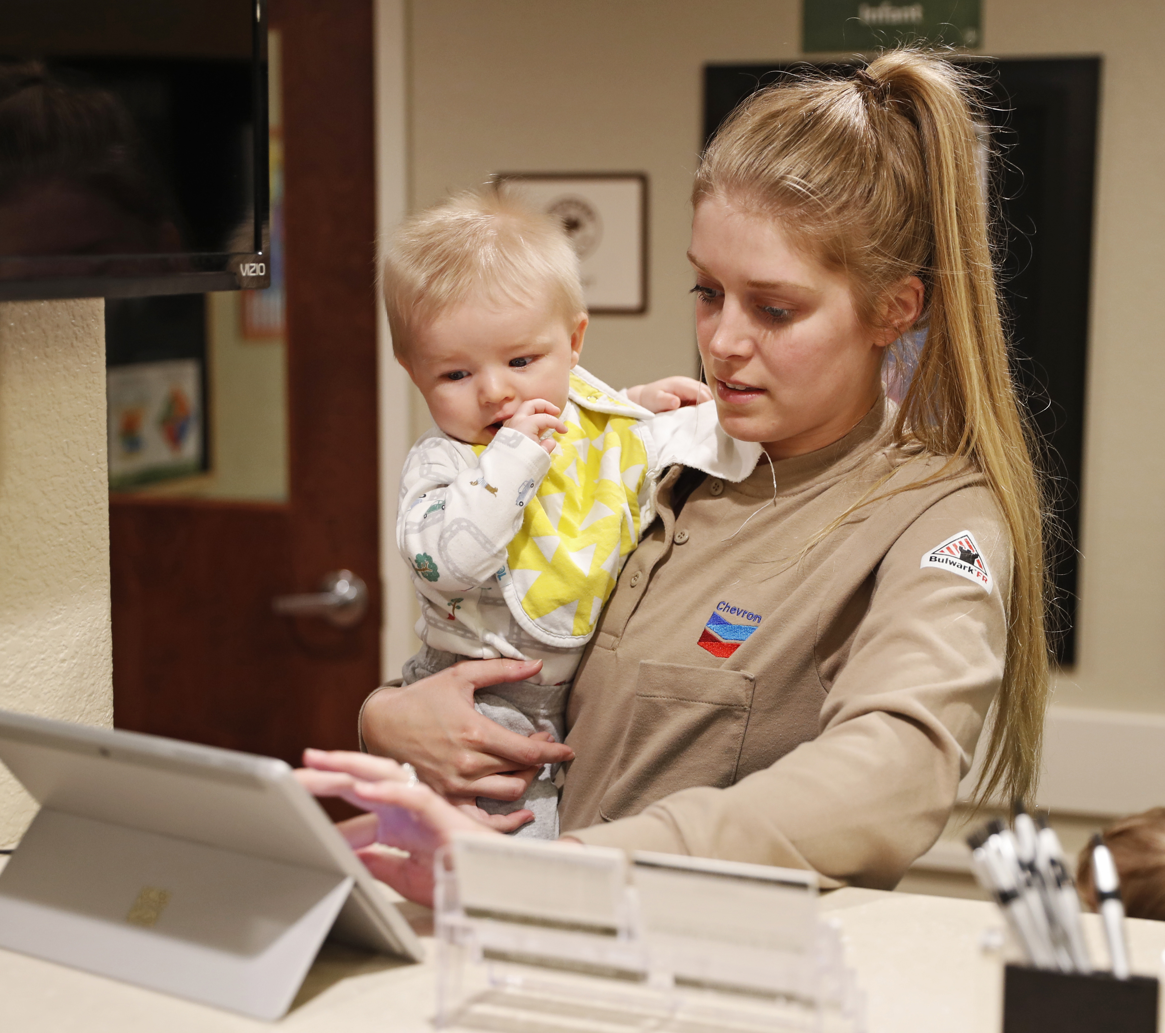 Image of women holding a child and looking at an ipad