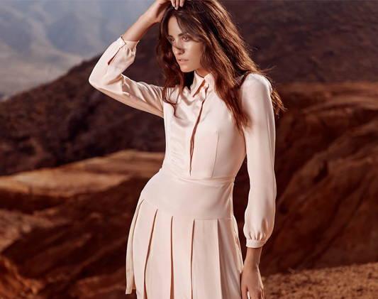 a woman wears a long dress