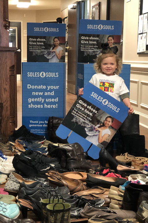 An Early Preschool student stands with over 80 pairs of shoes!
