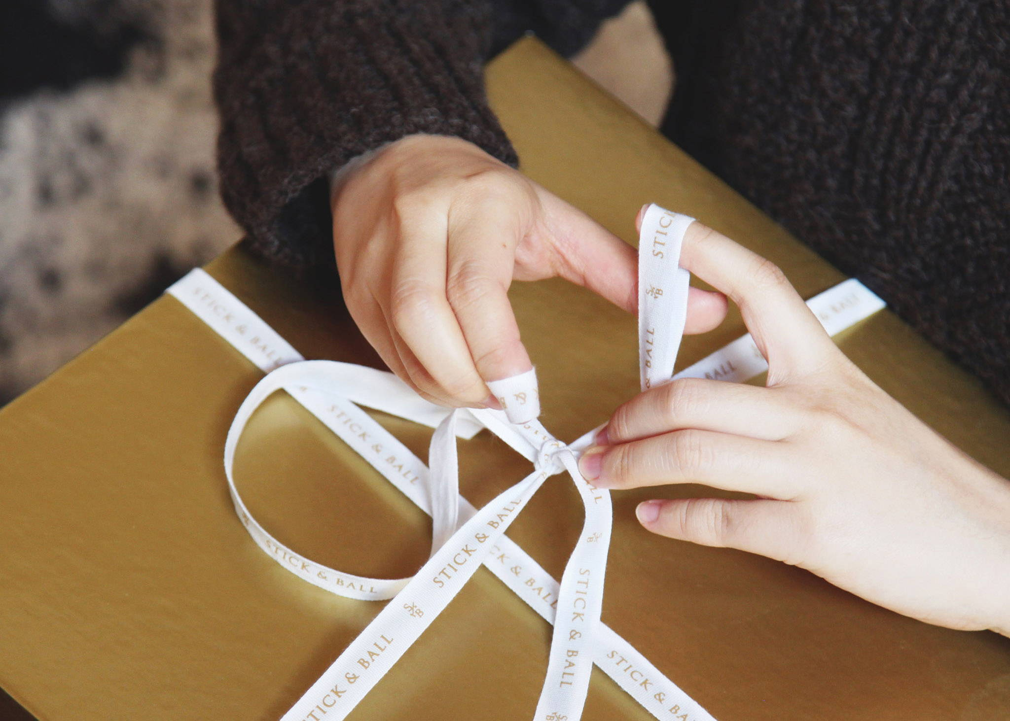 Woman tying Stick & Ball Ribbon around a gold box for a Christmas present
