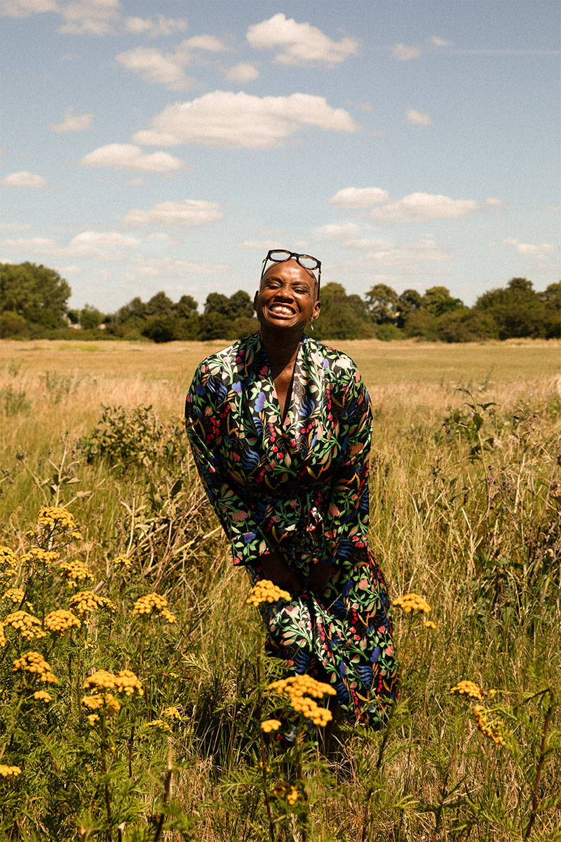 Andi Oliver Wearing YOLKE Anais Black Silk Dressing Gown standing in a field of flowers