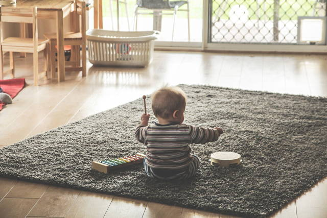 baby playing toy drum on a footcloth