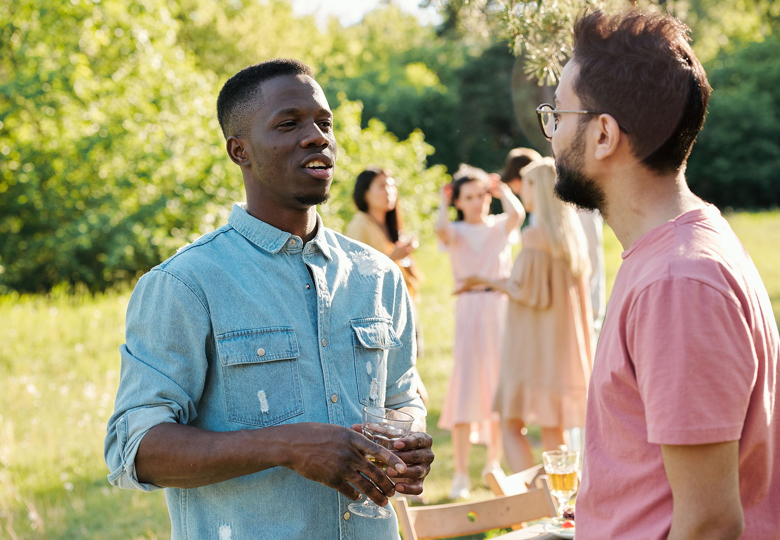 Photo of a young black and white man with glasses talking to each other at a friend reunion with girl friends in the background it a park.