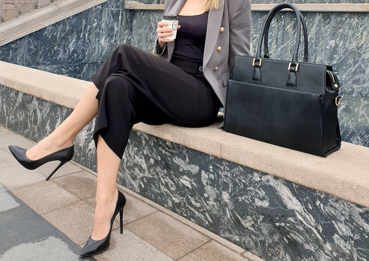 Business women sitting with a coffe in one hand, next to a leather laptop bag