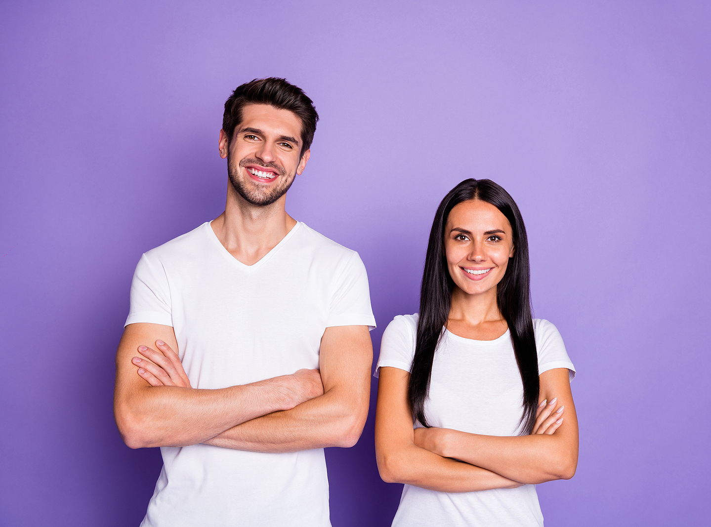 Image of an attractive man and woman of mixed ethnicities standing side by side with their arms crossed and a white tshirt, smiling against a purple background.
