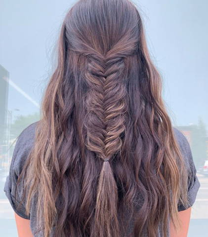 backview of a brunette woman with her hair down and braided