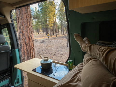 A person laying in a van parked in the woods with the door open
