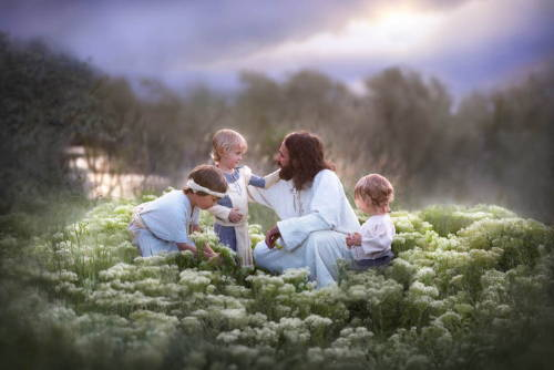 Jesus with small children in a field of white flowers.