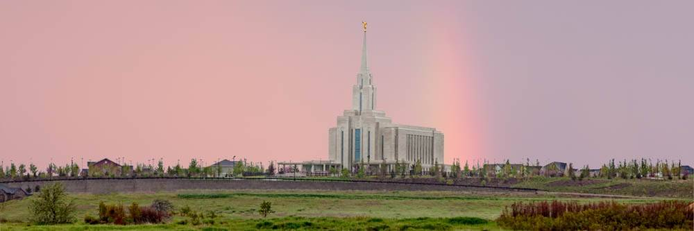 LDS art panoramic photo of the Oquirrh Mountain Temple against a pink sky and a rainbow.