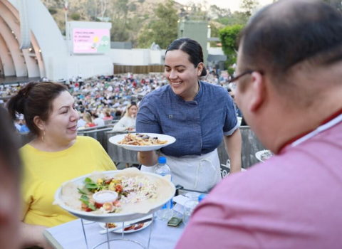 Patrons enjoying a sunny day at the Bowl, being served a delicious Food + Wine meal in their box seats