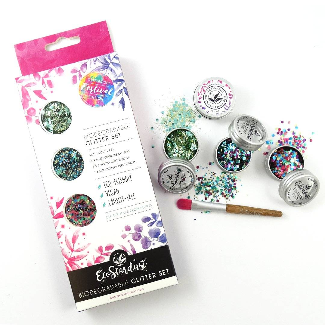Image shows our festival glitter set with 3x multicoloured glitter blends. Image shows the box, as well as the pots of glitter opened with some glitter spilled over the edge onto the table, as well as our vegan bamboo application brush.