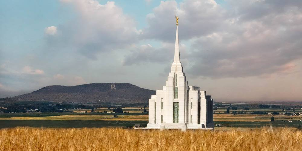 Photo of the Rexburg Temple behind an autumn field with the Rexburg hills in the background.