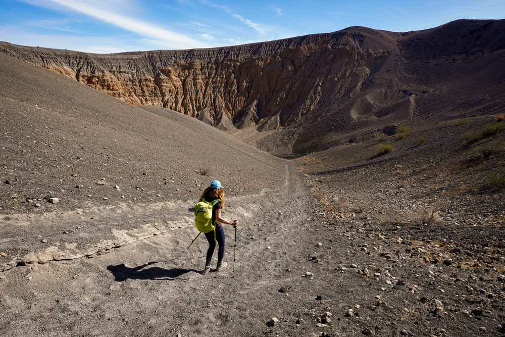 Woman hiking down a trail to Ubehebe Crater in Death Valley National Park