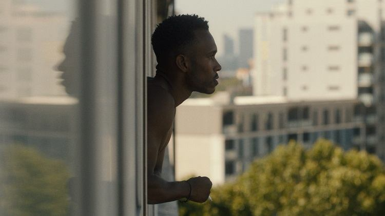 A man leans on the windowsill of a high-rise flat while smoking a cigarette.