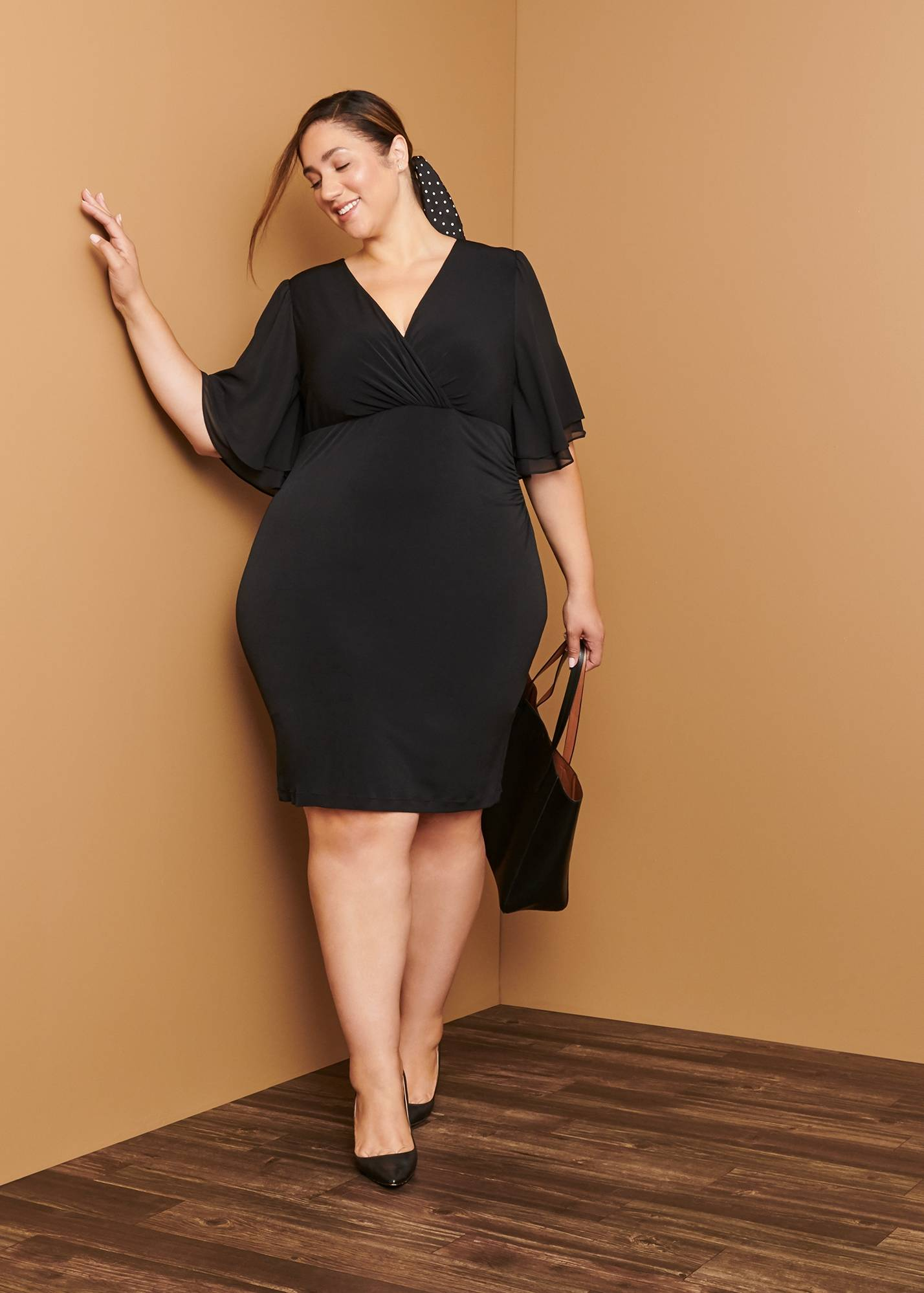 plus size woman in black bat wing sleeve work dress on day to night connected apparel blog