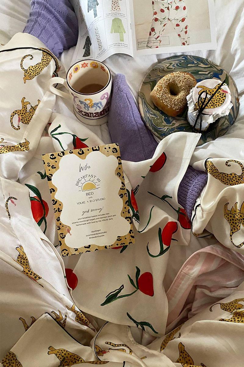 Willow Crossley has breakfast in bed in YOLKE Prowling Leopard Pyjamas