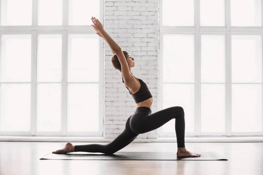 woman holding yoga pose in sunny room