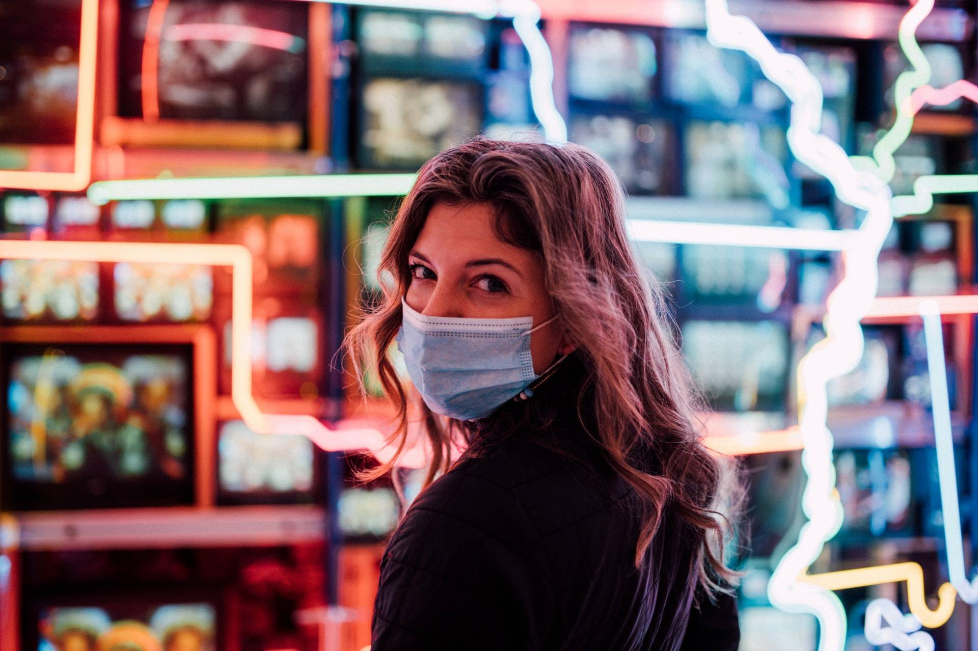 woman with medical mask looking back over her shoulder