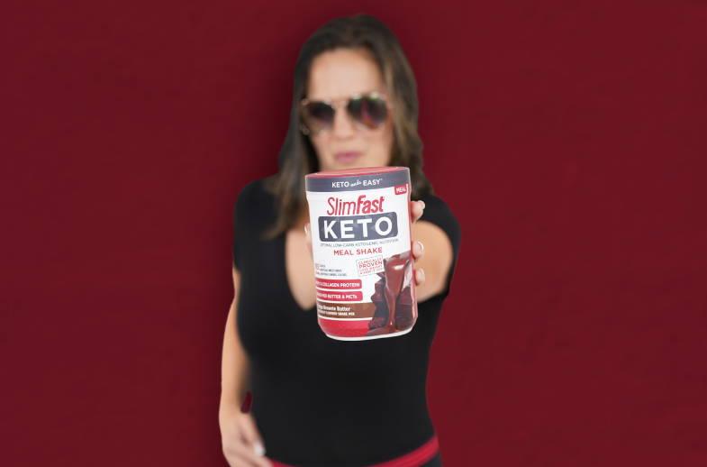 Keto Shake Mix- lifestyle image of lady holding a canister