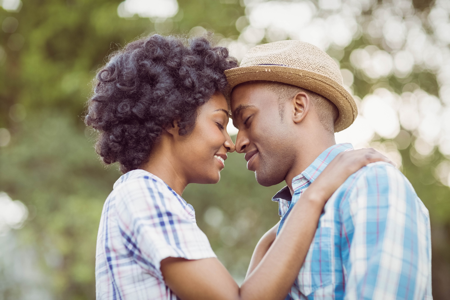 Photo of a young hip black couple with their eyes closed holding each other.