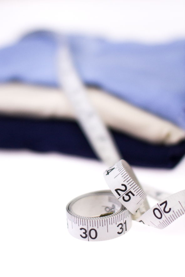 Image of three undershirts with a tape measure