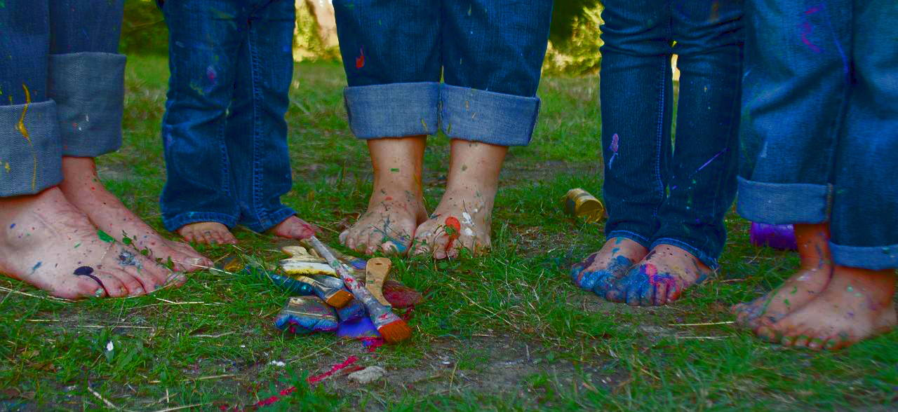 Family of feet covered with paint.