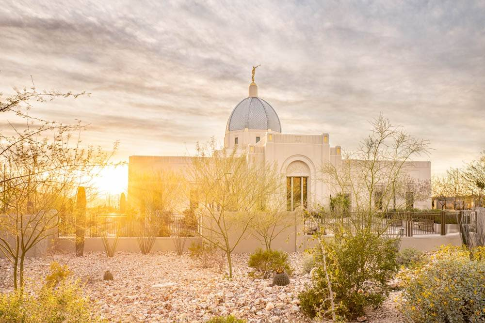 The sun crests over the edge of the Tuscon Arizona LDS Temple, which is surrounded by desert landscape.