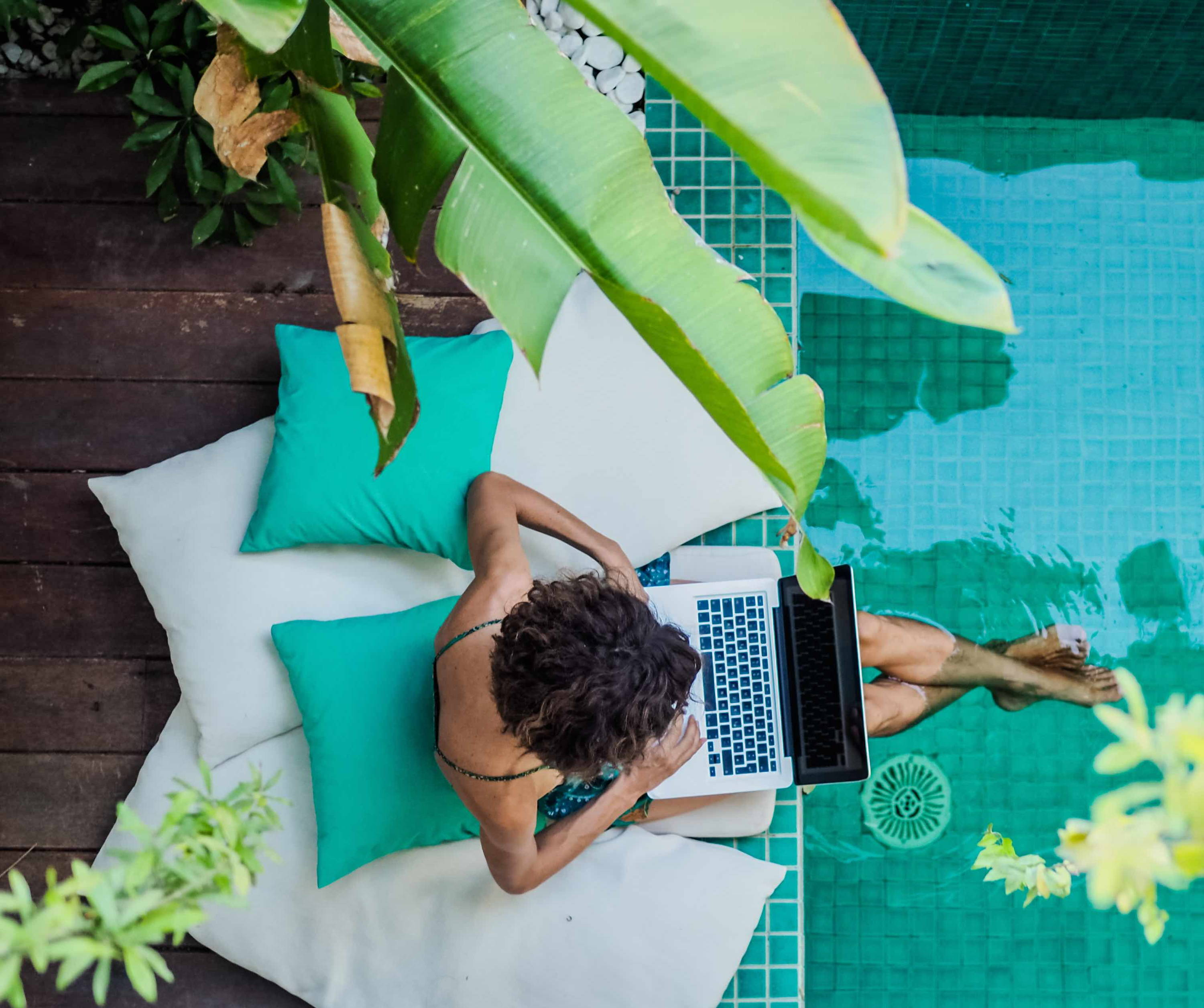 Woman with computer by pool