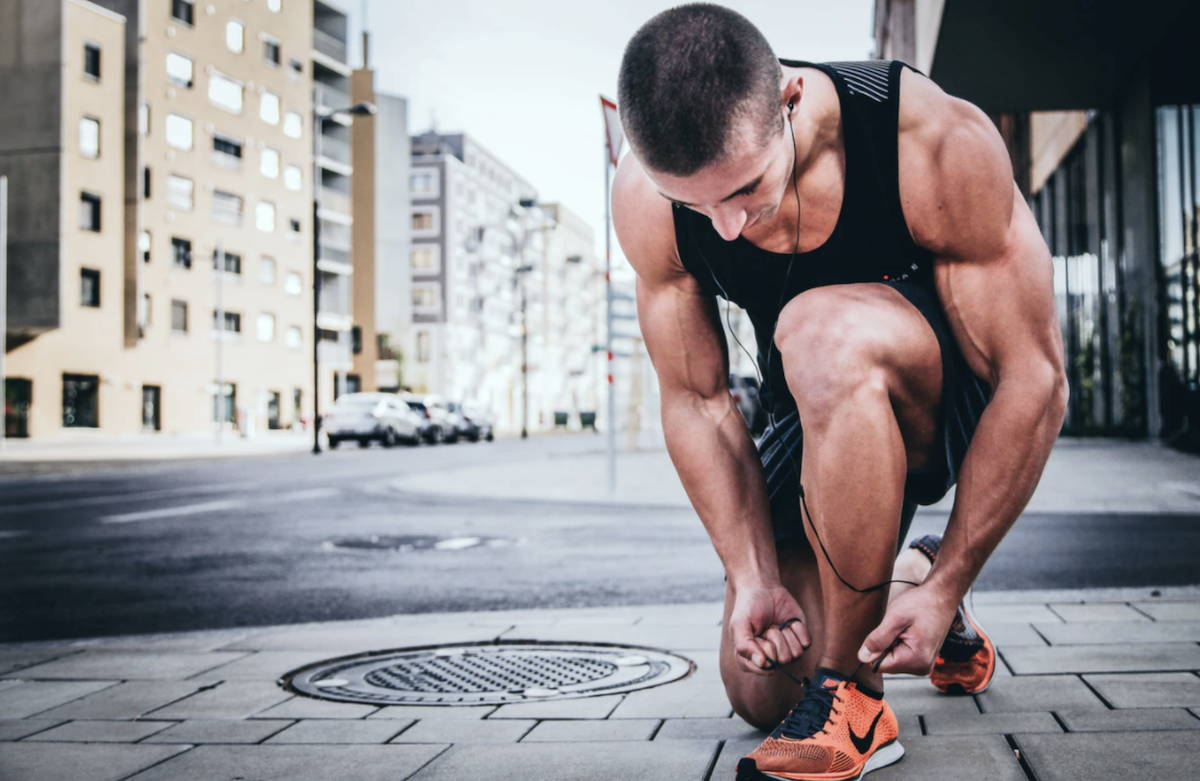 A man laces his shoes before going on a run.