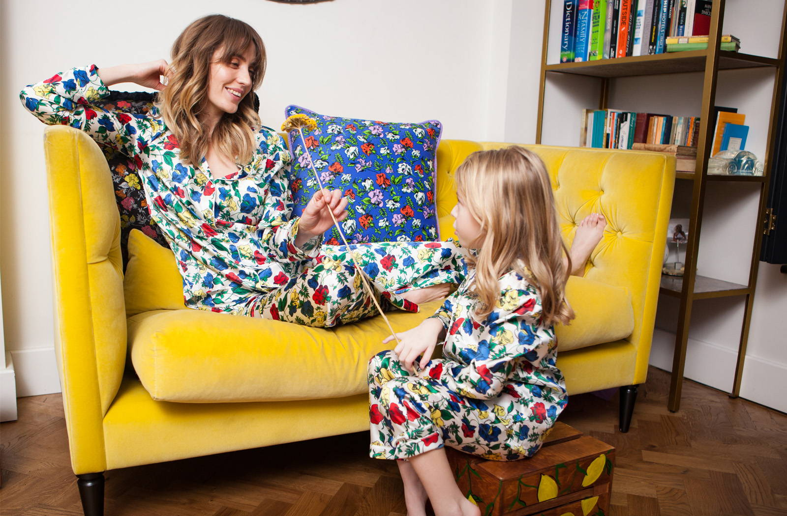 Luna and Tara Griffin sat on yellow sofa in in YOLKE Dakota Meadow Classic Silk Pyjama Set Meadow