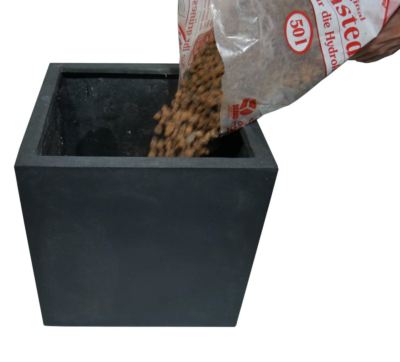 Pflanzgefäß wird mit Blähton aufgefüllt