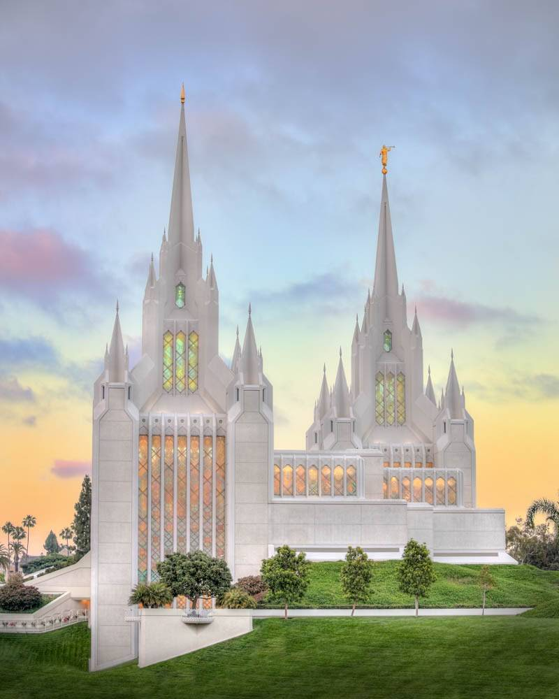Vertical photo of the San Diego Temple from the side, focusing on the colorful windows and tall steeples.