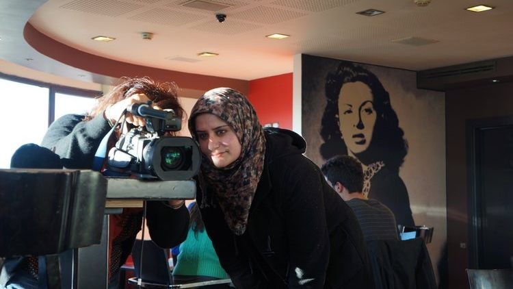 Two young women, one wearing a hijab, filming using a video camera