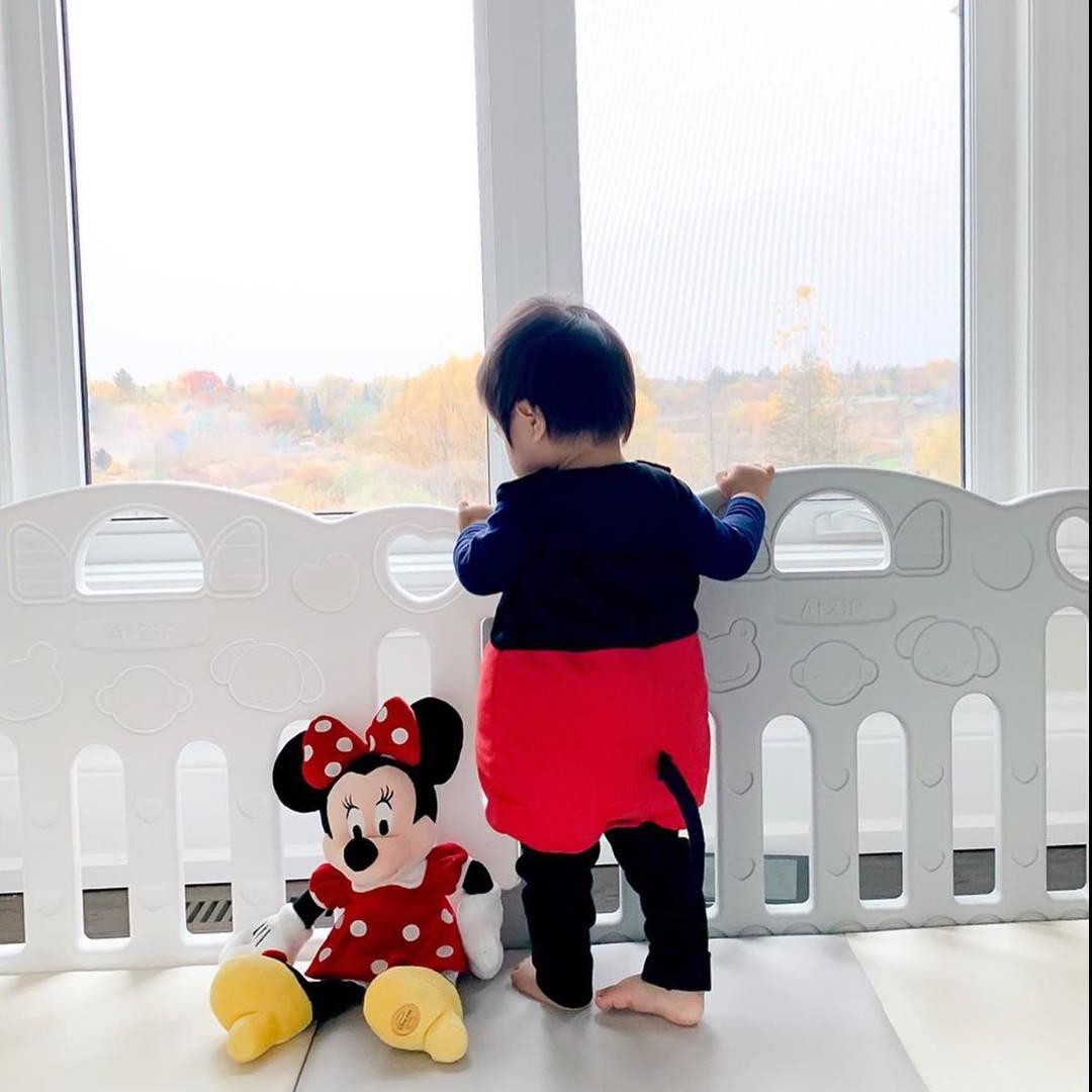 Baby milestone standing on AlZiP mat with baby room playpen