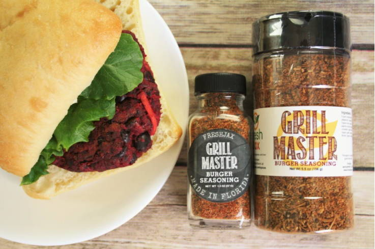 A plate with a beet burger next to two bottles of FreshJax Organic Grill Master Burger Blend.