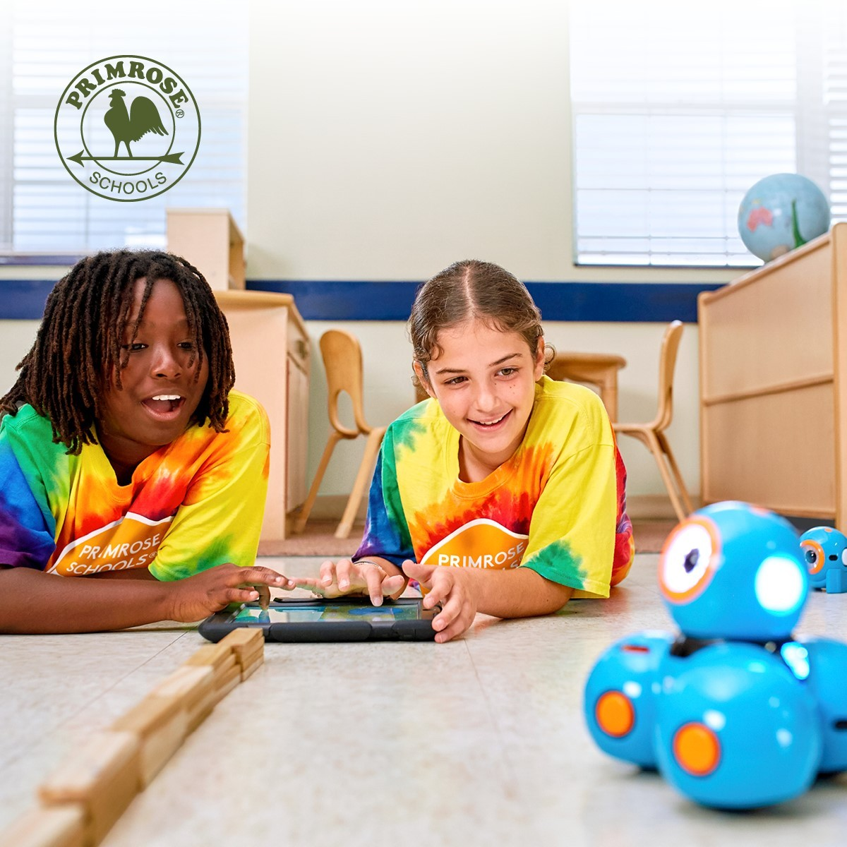 two Explorer students driving a robot through the classroom