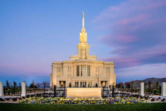 Photo of the Payson Utah Temple behind a yellow and purple flowerbed.