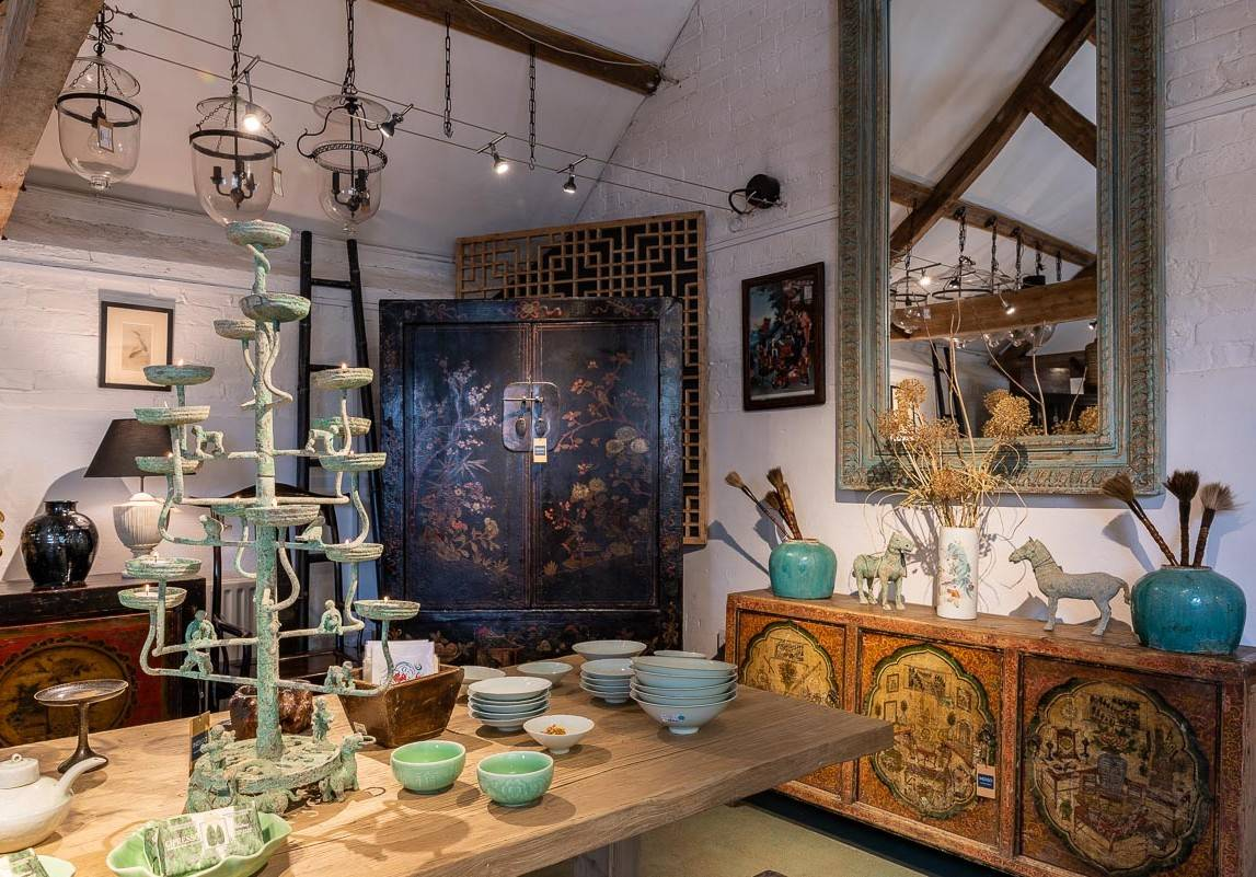 A corner of the Indigo Antiques showroom featuring various Chinese antiques including a 19th century Black Lacquer Wedding Cabinet & a one of a kind Victorian influenced Mongolian sideboard from the 19th century.