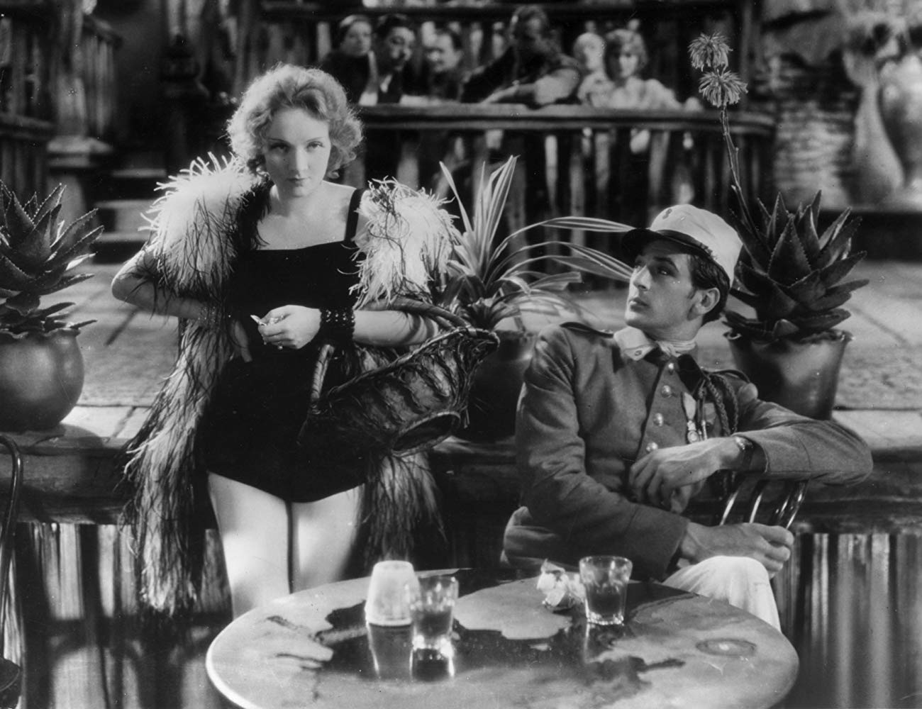 Marlene wearing a performance outfit revealing her legs, standing next to a soldier at a bar.