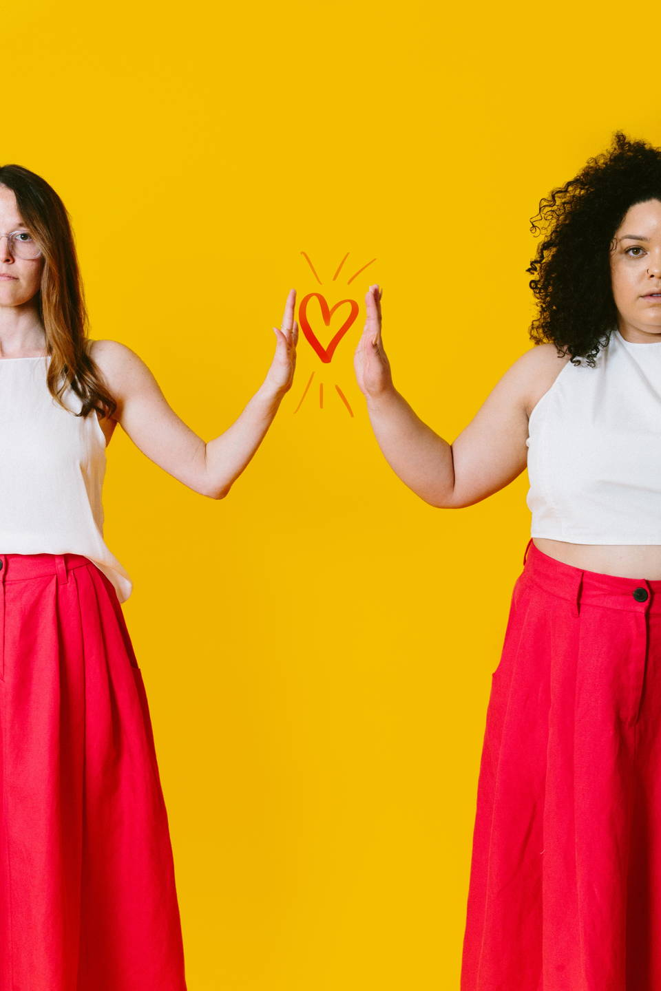 two women wear matching red floor-length skirts and white tank tops. They are standing in front of a yellow background, and each has one hand held up mirroring the other woman. there is a red heart drawn between.