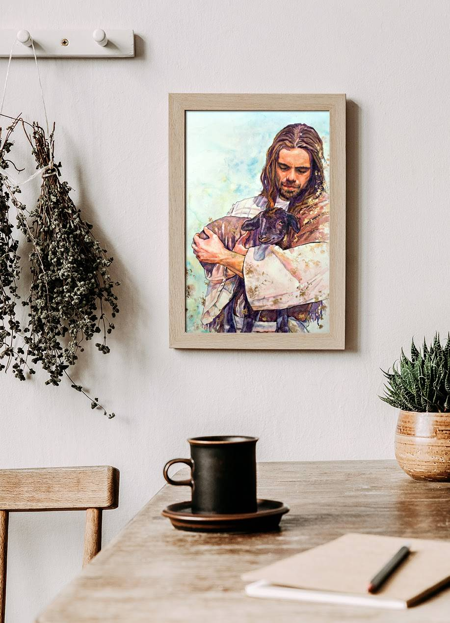 A small art portrait of Jesus holding a sheep. The picture is hung on the wall at the end of a kitchen counter.