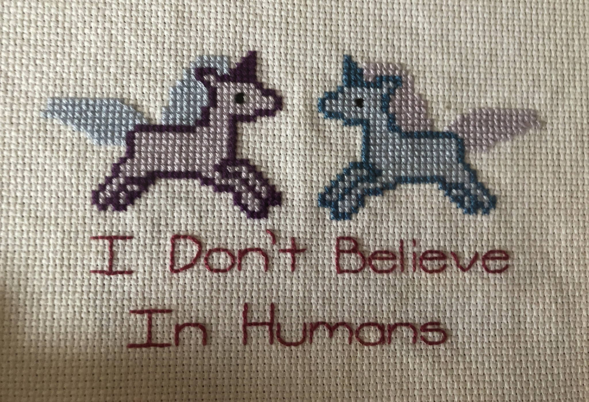 Stitching of two unicorns facing eachother with the words I don't believe in humans, underneath them.