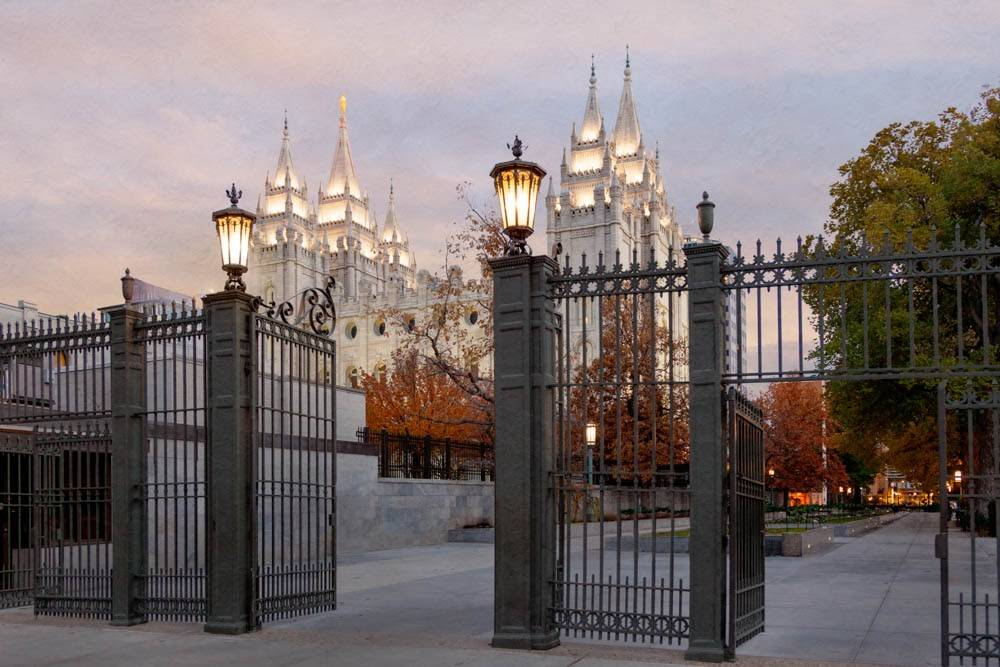 Distant photograph of the Salt Lake City Utah LDS Temple from behind entrance gates.