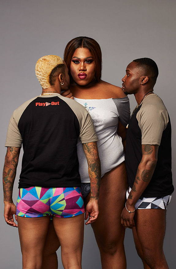 Three black trans models stand together wearing play out underwear and t-shirts.